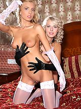 Gorgeous girls Malgina and Kira strip each other down to their stockings on the bed.